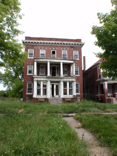 back on the mainland: a 3 story, 6 apartment brick house with Georgian double front porches: twelve white columns  sagging like a mouth